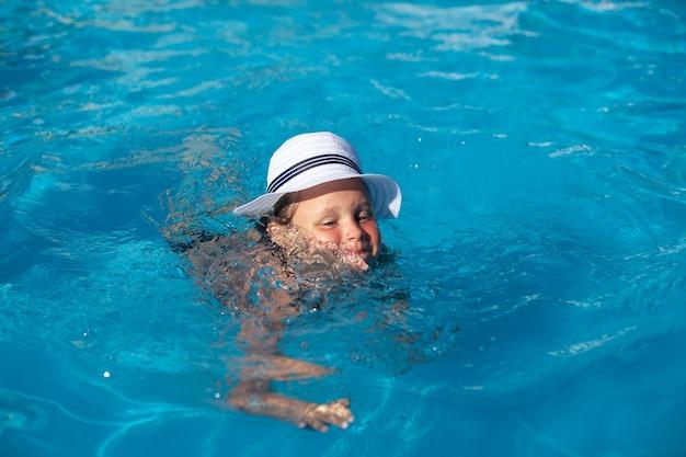 Bambino in cappello di paglia bianco felice ragazza affascinante sta imparando a nuotare in piscina e godendosi il riposo in estate calda...