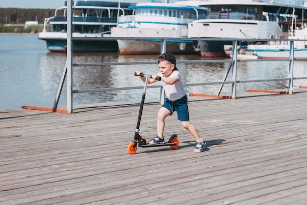Un bambino in una maglietta bianca pantaloncini blu e berretto nero cavalca uno scooter su un molo di legno sullo sfondo dei traghetti
