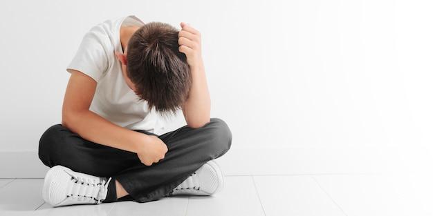 Un bambino la cui depressione è seduta per terra