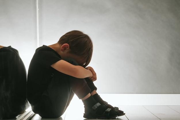 Bambino la cui depressione è seduta sul pavimento