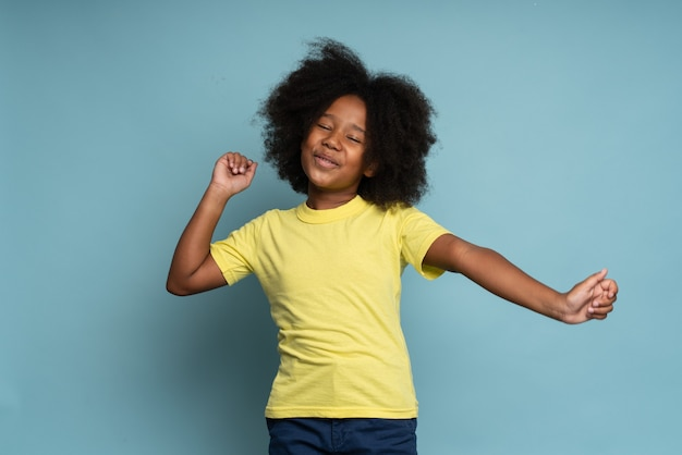 Bambino vincente, successo. ritratto di una bambina eccitata in maglietta che alza le mani e si sente felice della vittoria e della fortuna, esprimendo gioia estrema. colpo dello studio dell'interno isolato su fondo blu