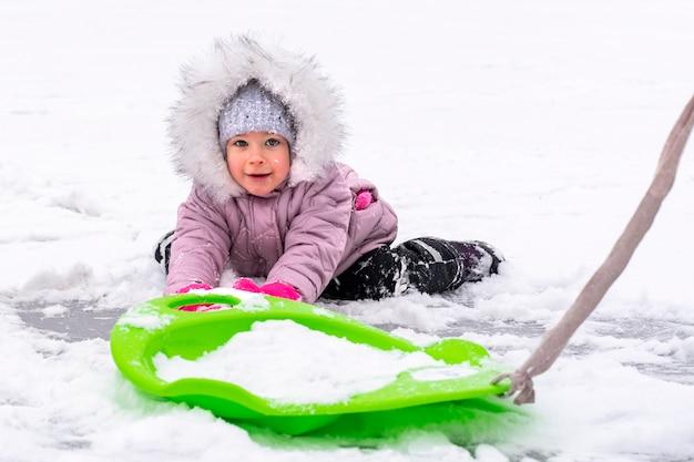 Bambino in abiti invernali che gioca con le slitte nella neve