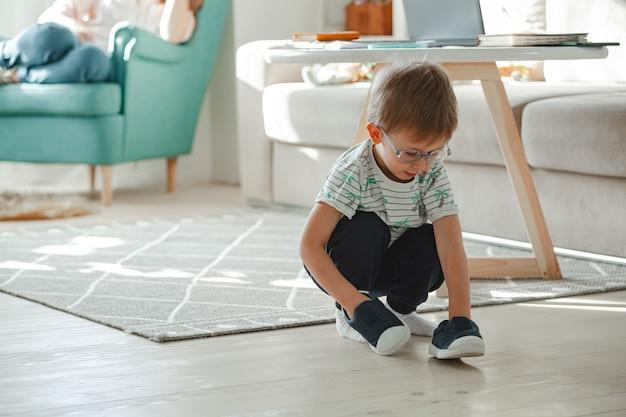 Il bambino con autismo con gli occhiali gioca con le sue scarpe