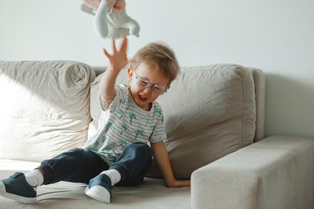 Un bambino con autismo con gli occhiali siede sul divano e triste, arrabbiato a