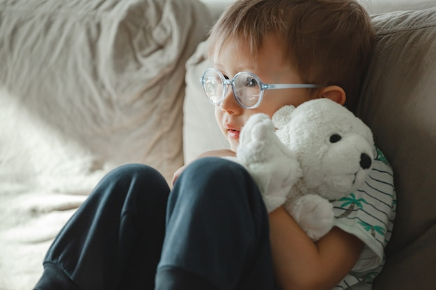 Un bambino con autismo con gli occhiali si siede sul divano e triste