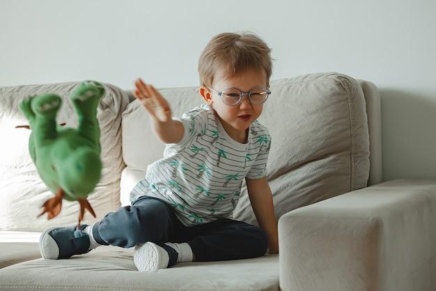 Bambino con autismo con gli occhiali si siede sul divano e triste