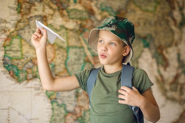 Bambino con uno zaino sulla schiena, sogna di viaggiare, lancia in aria un aeroplano di carta