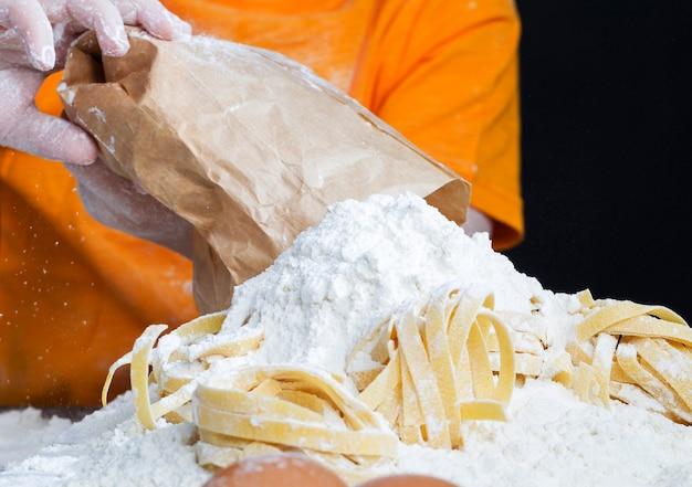 Un bambino con un sacco di farina e pasta con cui prepara il cibo