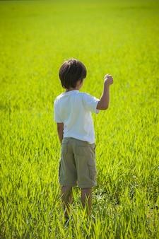 Bambino con palloncino in piedi nel campo verde
