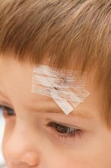 Un bambino con un cerotto sulla fronte cucita in un incidente
