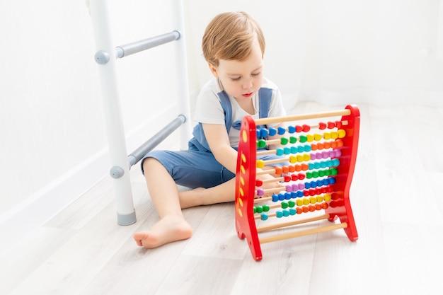 Un bambino con le bollette a casa, un ragazzo carino che gioca o conta sulle bollette.