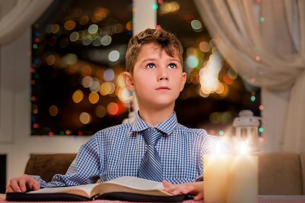 Bambino con libro guardando in alto. ragazzo con libro di notte. riflessivo giovane lettore. libro di lettura alla vigilia di natale.