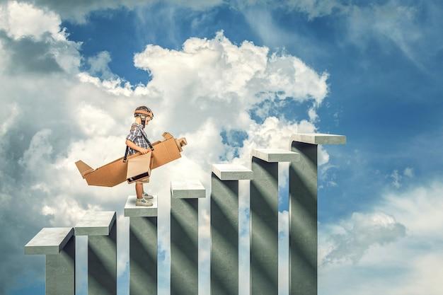 Bambino con l'aeroplano di cartone sulla scala di cemento astratta