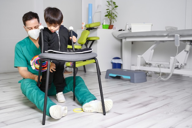 Bambino con paralisi cerebrale in fisioterapia in un centro di terapia per bambini.
