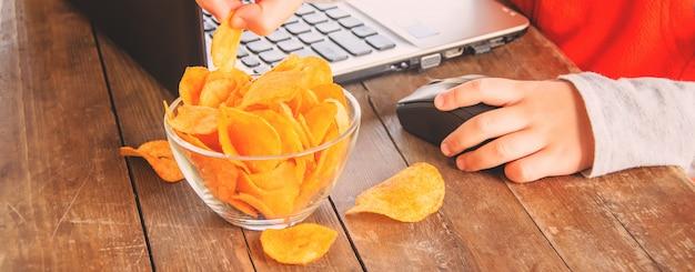 Bambino con patatine fritte dietro un computer. messa a fuoco selettiva.