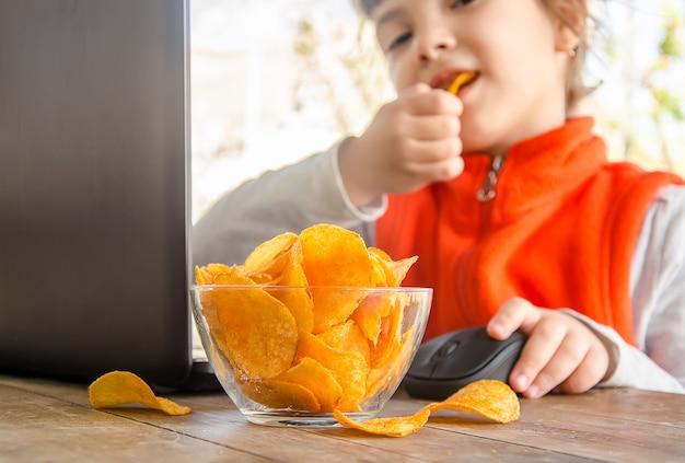 Bambino con patatine fritte dietro un computer