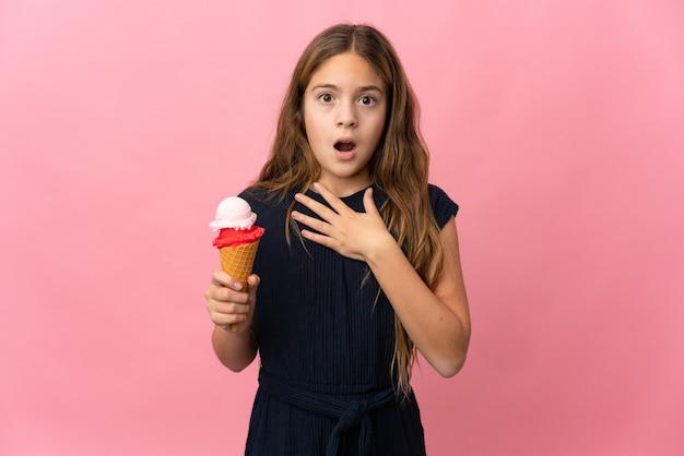 Bambino con un gelato alla cornetta su sfondo rosa isolato sorpreso e scioccato mentre guarda a destra