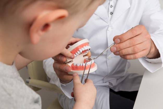 Bambino con il dentista che considera insieme la mascella falsa nell'armadietto.