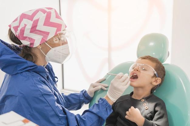 Un bambino con un dentista in uno studio dentistico. cure odontoiatriche in una clinica per bambini.