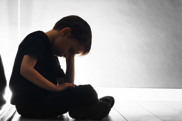 Il bambino con depressione è seduto sul pavimento