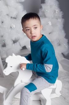 Un bambino con sindrome di down con albero di natale