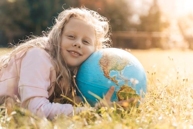 Bambino con globo terrestre ritratto di una ragazza bionda europea della scuola elementare con un g...