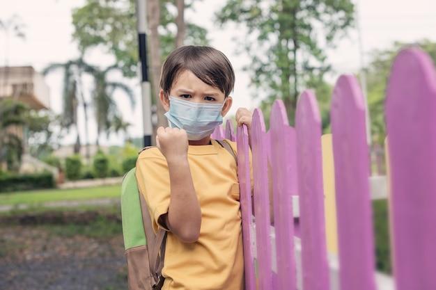 Bambino con maschera facciale torna a scuola dopo la quarantena e il blocco del covid-19.