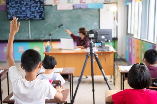 Bambino con maschera facciale che torna a scuola dopo la quarantena e il blocco del covid-19 i bambini asiatici indossano la maschera come protezione dal coronavirus covid-19 nella scuola