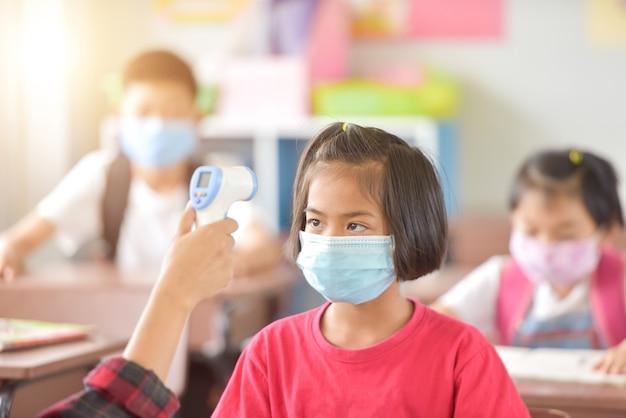 Bambino con maschera facciale che torna a scuola dopo la quarantena e il blocco del covid-19. i bambini asiatici indossano la maschera per proteggersi dal coronaviruscovid-19 a scuola. ritratto di studente tailandese.