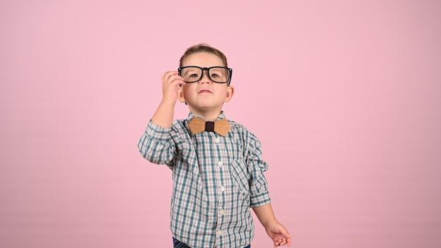 Bambino con gli occhiali, su uno sfondo rosa. foto di alta qualità