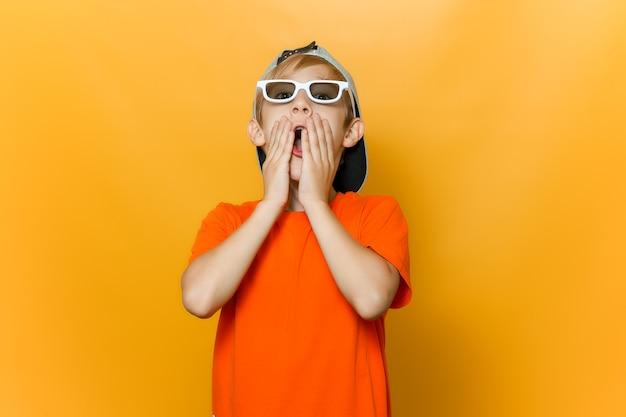 Un bambino con gli occhiali per guardare film si copre la bocca con le mani è molto spaventato