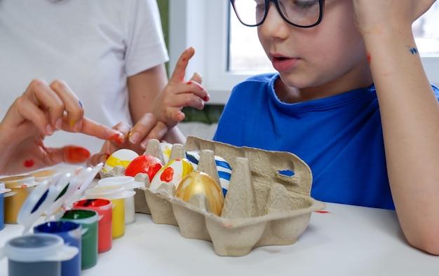 Un bambino con sua madre ha dipinto le uova con la vernice il bambino guarda le uova decorate con le sue