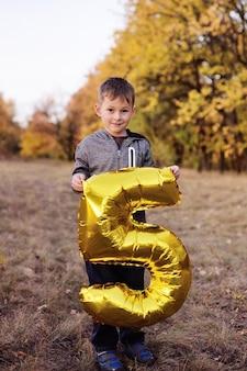 Un bambino con un grande palloncino a forma di numero cinque sullo sfondo della foresta d'autunno.