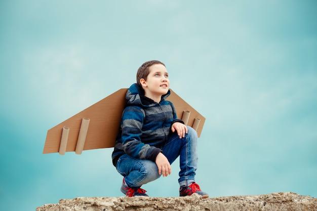 Bambino con ali di aeroplano di carta