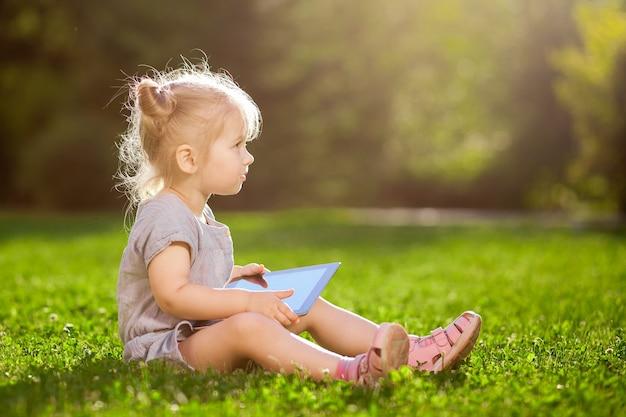 Bambino con un tablet seduto nel parco