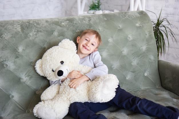 Bambino con un orsacchiotto. ragazzo divertente sul divano
