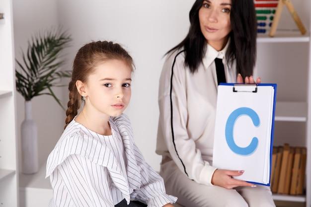 Bambino con terapista che lavora sulla pronuncia e sui suoni insieme seduti in classe. Foto Premium