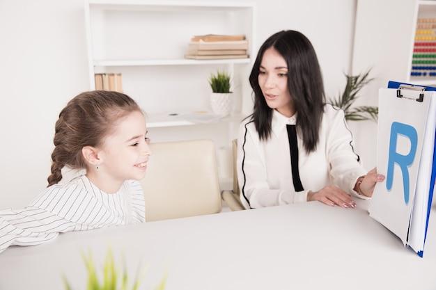 Bambino con terapista che lavora sulla pronuncia e sui suoni insieme seduti in classe.