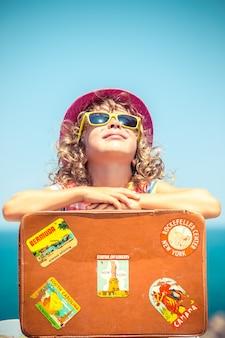 Bambino con valigia vintage in vacanza estiva concetto di viaggio e avventura