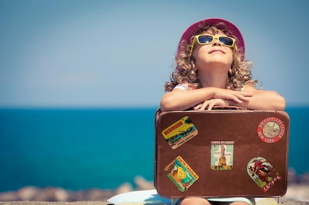 Bambino con la valigia vintage in vacanza estiva. concetto di viaggio e avventura