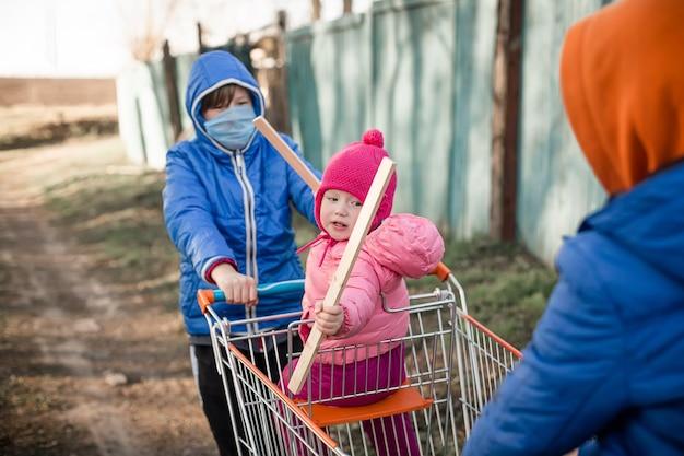 Bambino senza maschera protettiva dopo lo shopping nel carrello del supermercato concetto di coronavirus