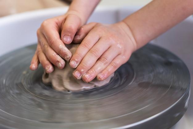 Un bambino lavora con l'argilla sul tornio da vasaio