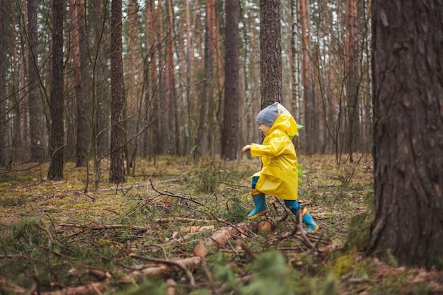 Il bambino con l'impermeabile giallo cammina nella foresta dopo la pioggia e il divertimento