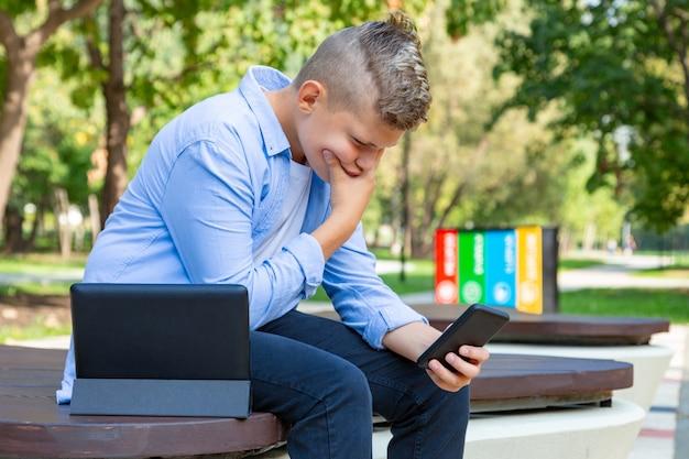 Infanzia, realtà aumentata, tecnologia e concetto della gente - il ragazzo con un fronte imbarazzato esamina lo smartphone all'aperto all'estate