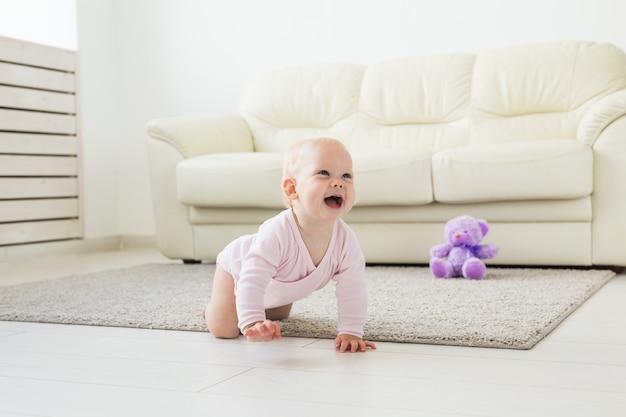 Concetto di infanzia, bambini e prima infanzia - neonata divertente strisciante al chiuso a casa