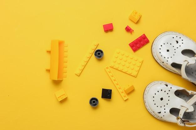 Concetto di infanzia mattoni giocattolo sandali per bambini