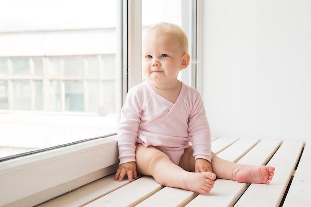 Concetto di infanzia, famiglia e neonato - piccola neonata sul davanzale della finestra a casa