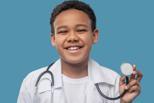 Infanzia, gioia. felice ragazzo ridente dalla pelle scura in camice bianco che mostra uno stetoscopio medico su sfondo blu in studio
