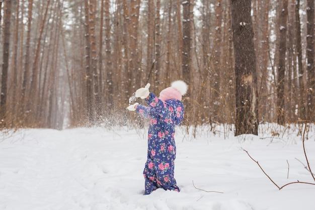 Concetto di infanzia e persone - ragazza bambino che cammina in inverno all'aperto e lancia la neve