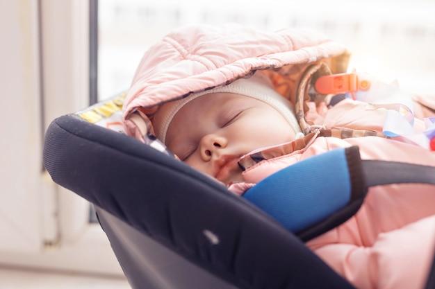 Infanzia e concetto di sicurezza - neonata che dorme nel seggiolino per bambini.